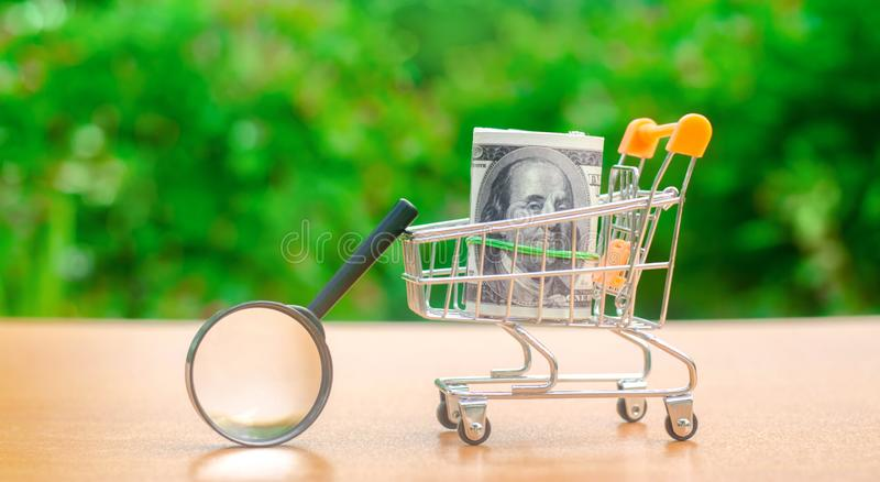 Dollar sedlar i en shoppa spårvagn och förstoringsglas Begreppet av att finna k?llor av investeringen och sponsorer Finna a royaltyfria bilder