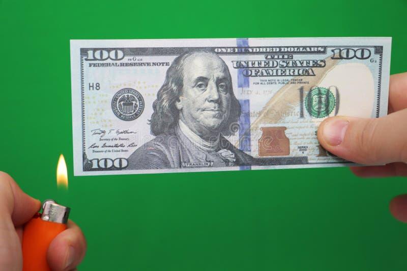 100 dollar som bränner på en grön bakgrund Begrepp av nedgång i ekonomi och förlust royaltyfria bilder