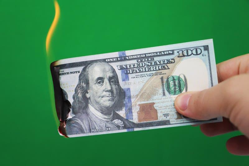 100 dollar som bränner på en grön bakgrund Begrepp av nedgång i ekonomi och förlust royaltyfria foton