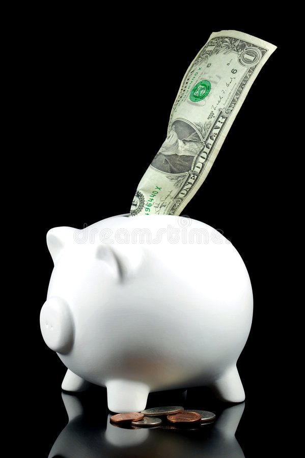 Dollar and some change. Piggy bank with One dollar and some change, isolated on black stock photos