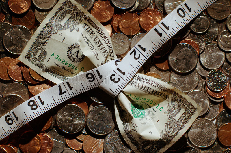 Dollar Squeeze. Dollar bill being squeezed by tape measure on money background royalty free stock photo
