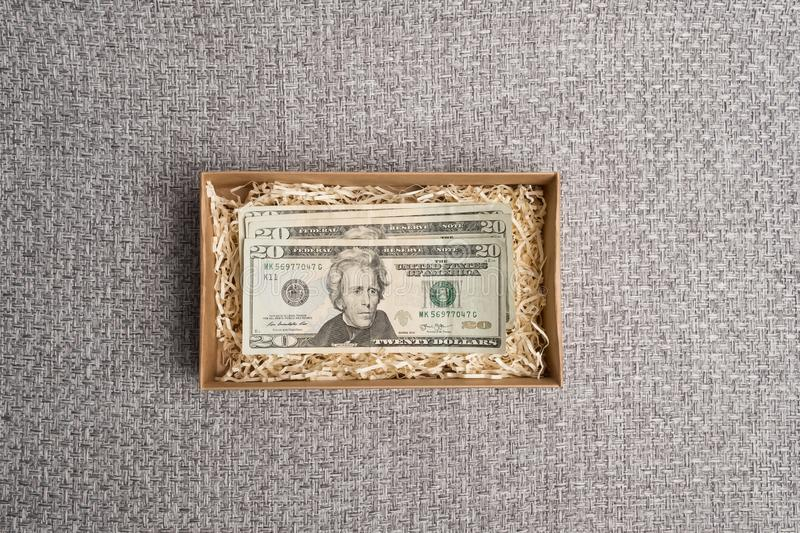 Cardboard box with american money. Banknotes in a small gift cardboard box. Dollar studio image. Notes in a carton box. Cardboard box with american money stock photography
