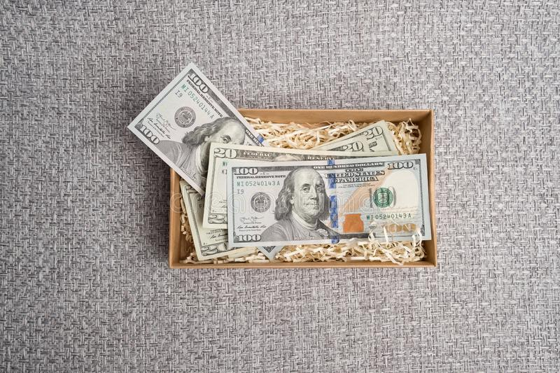 In a carton box. Cardboard box with american money. Banknotes in a small gift cardboard box. Dollar studio image. Notes in a carton box. Cardboard box with royalty free stock photos