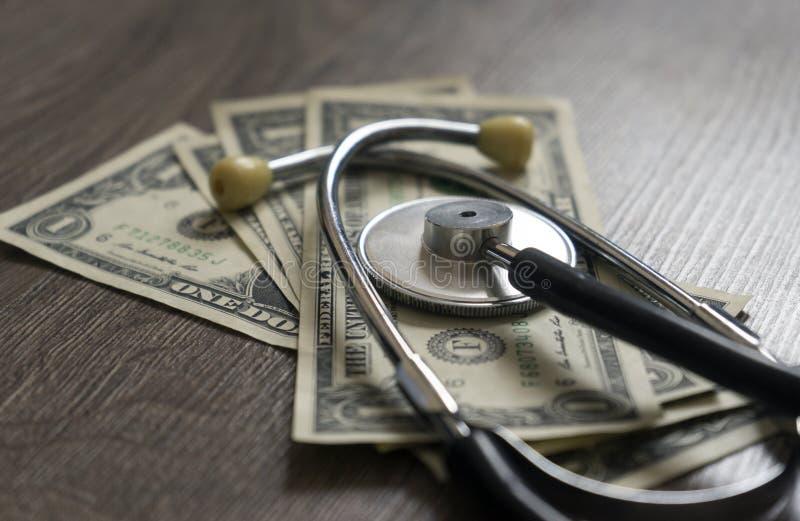 Dollar und ein Stethoskop lokalisiert auf einem hölzernen Hintergrund stockbilder