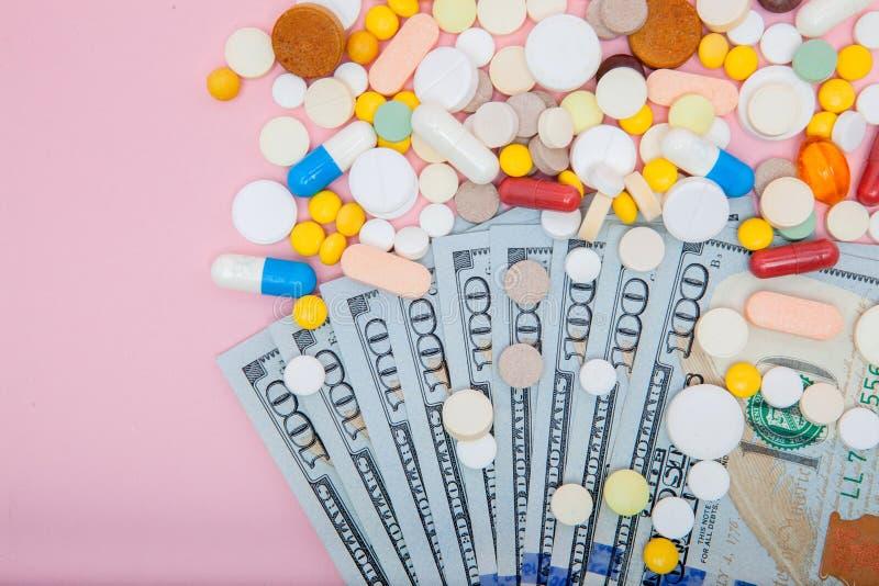 Dollar und Pillen auf einem rosa Hintergrund Verordnungsmedizin auf Dollar für Pharmaindustriekonzept von hohen Kosten für heilt lizenzfreie stockfotos