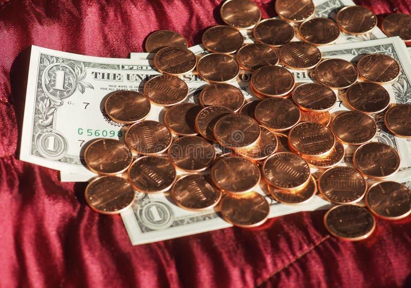 Dollaranmärkningar och mynt, Förenta staterna över röd sammetbakgrund arkivfoto