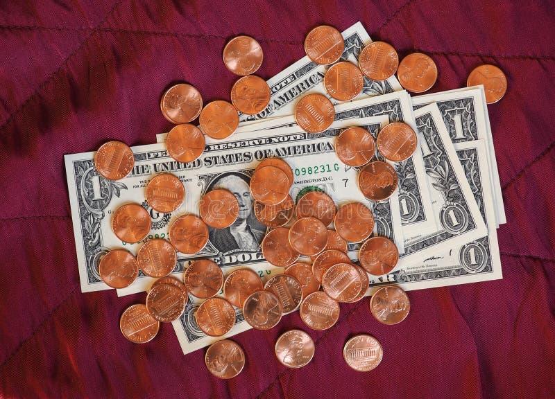 Dollaranmärkningar och mynt, Förenta staterna över röd sammetbakgrund royaltyfria foton
