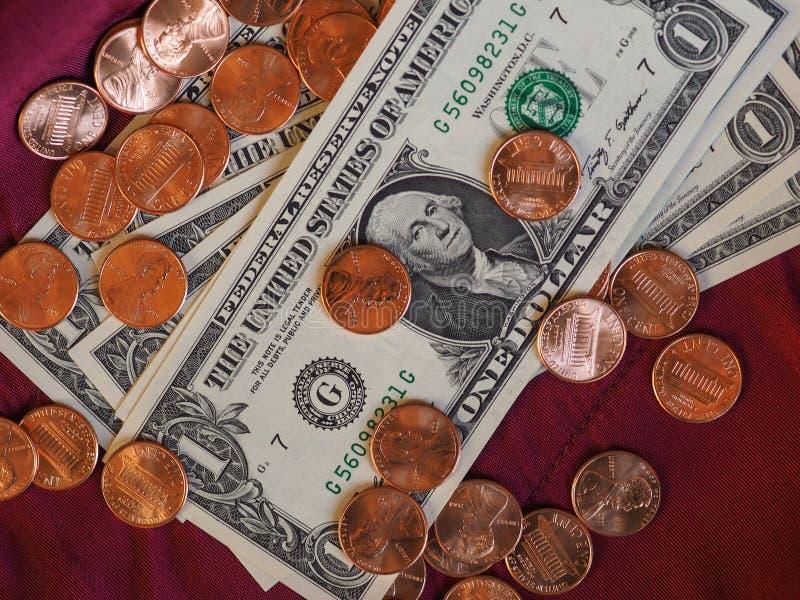 Dollaranmärkningar och mynt, Förenta staterna över röd sammetbakgrund arkivbilder