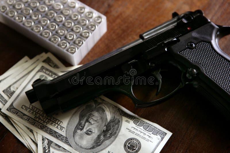 Dollaranmerkungen und Gewehr, schwarze Pistole stockfotos