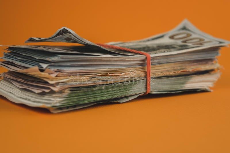 Dollarbündel auf orangefarbenem Hintergrund stockfotografie
