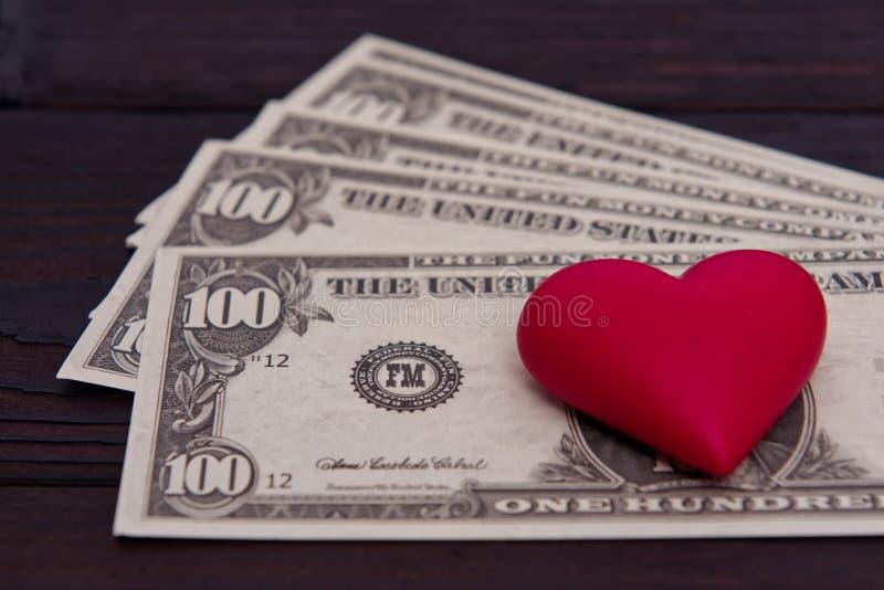 Dollarbankbiljetten en rood hart op een lijst stock foto