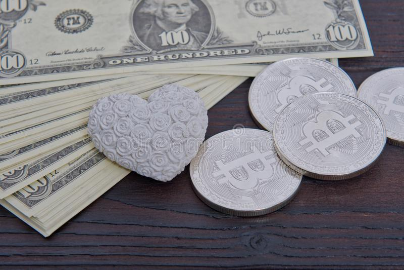 Dollarbanknoten, -bitcoins und -herz auf einer Tabelle lizenzfreies stockfoto