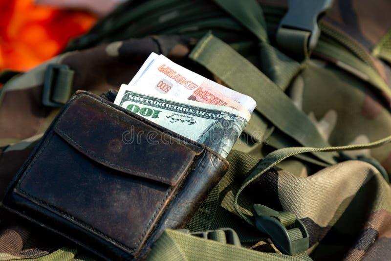Dollarbanknoten im Umschlag getrennt auf Weiß Geld von verschiedenen Ländern in einer Geldbörse gesetzt auf eine Militäruniform stockbild