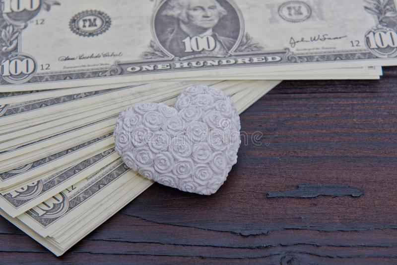Dollarbanknoten und -herz auf einem Holztisch stockfotos