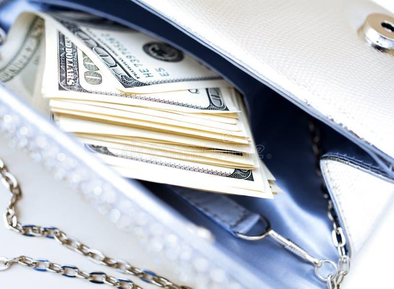 Dollarbills i en lyxig handväska arkivbild