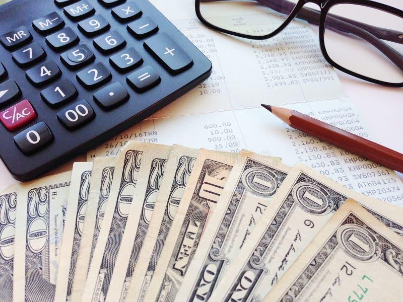 Dollargeld, calculator en het boek of de financiële staat van de besparingsrekening op bureaulijst royalty-vrije stock afbeelding