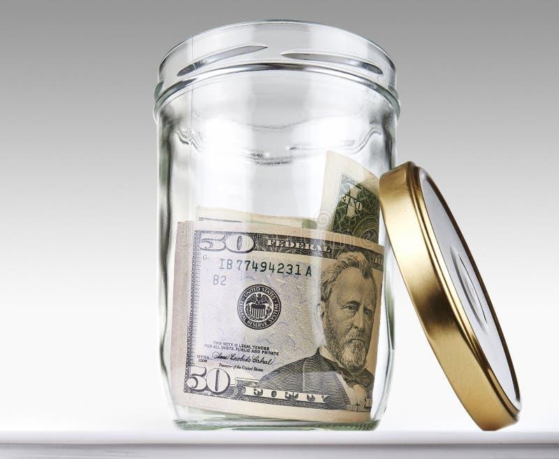 Dollari americani di banconote in un barattolo aperto vetro fotografia stock