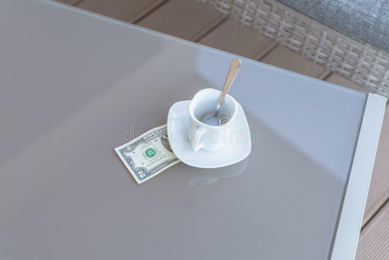Dollari di fattura americani e tazza di caffè vuota su una tavola di vetro del caffè all'aperto Pagamento, punta immagine stock libera da diritti