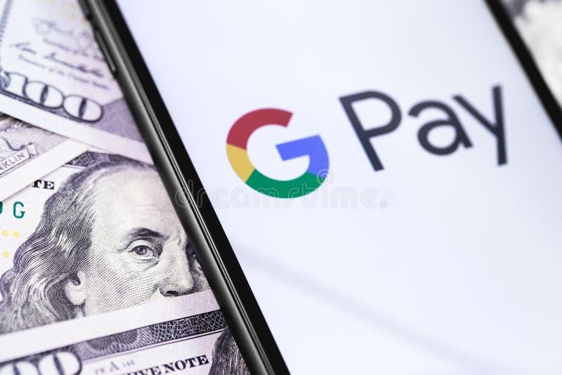 Dollari e smartphone con il logo di paga di Google sul servizio digitale del portafoglio dello schermo da Google immagine stock