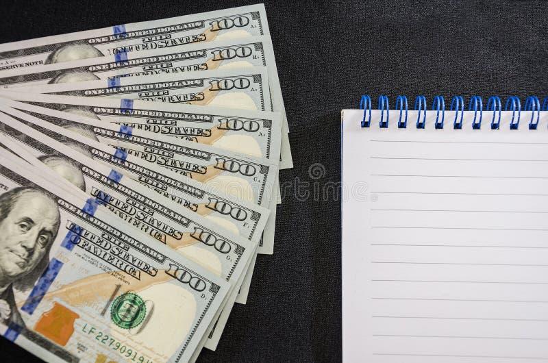 Dollari e taccuino su un fondo nero Primo piano Posto per testo immagine stock