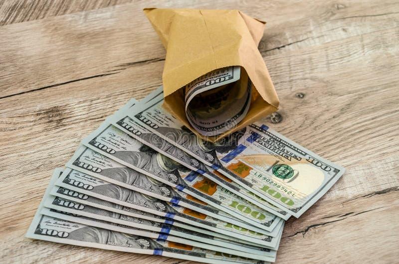 Dollari in un sacco di carta su un fondo di legno immagine stock libera da diritti