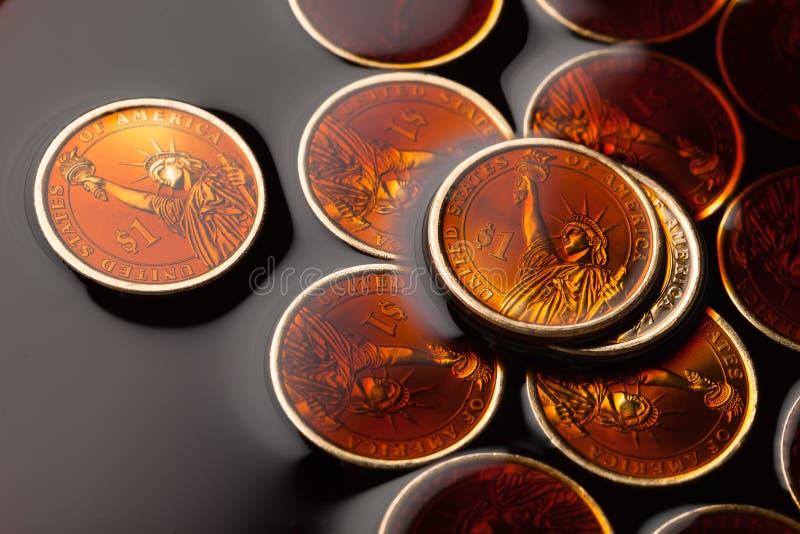 dollarmynt i råoljan royaltyfri fotografi