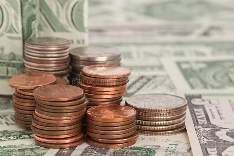 Dollarmynt på dollarräkningar royaltyfri bild
