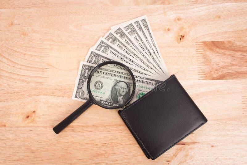 Dollarpengar i plånbok och förstoringsapparat royaltyfri foto