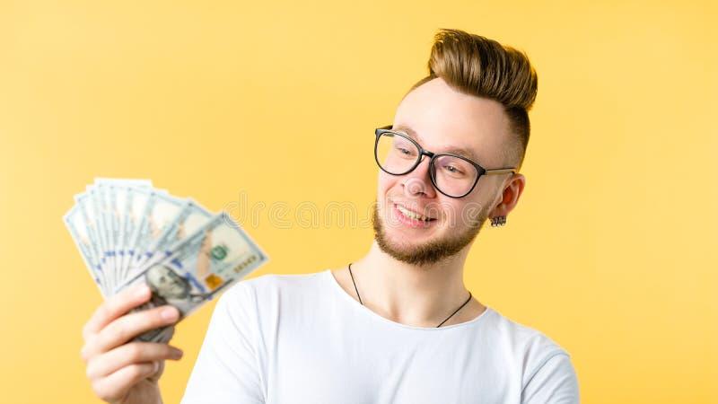 Dollarräkningar för ung man förvånade lyckligt frilansar arkivbild