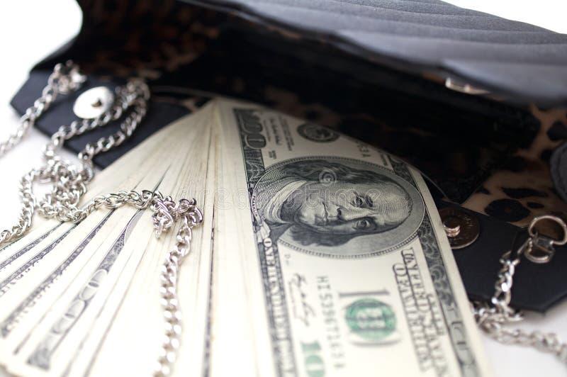 Dollarräkningar i en lyxig svart handväska, begreppsmässig bild royaltyfria bilder