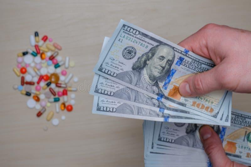 Dollarräkningar och kulöra piller på en ljus bakgrund Minnestavlapengarbegrepp arkivfoto