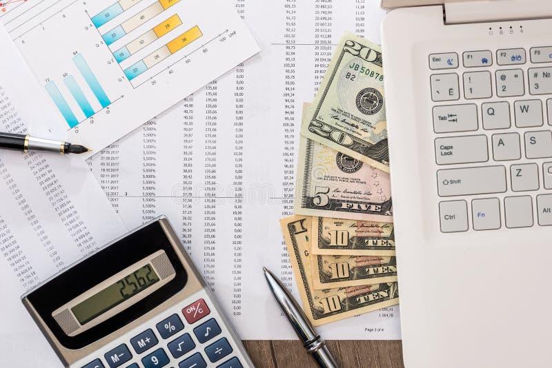 Dollarräkningar på en tabell med grafdiagrammet och bärbara datorn, penna arkivfoto