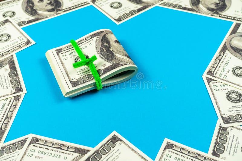 Dollarräkningar vikta i halva på ljust - blå bakgrund royaltyfri foto