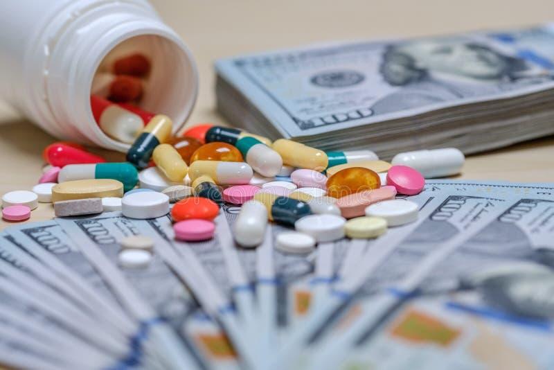 Dollarrekeningen en gekleurde pillen op een lichte achtergrond Het concept van het tablettengeld royalty-vrije stock fotografie