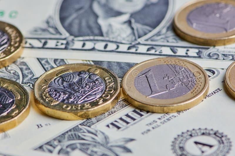 Dollarrekeningen met Euro en Pondmuntstukken samen stock foto's
