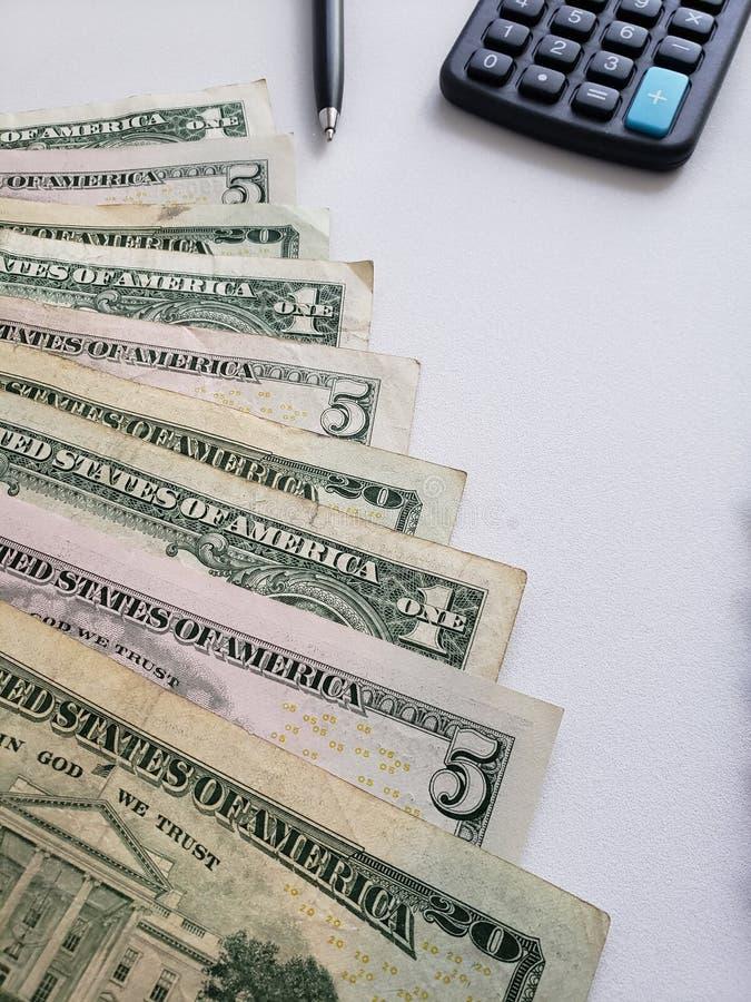 Dollars américains de billets de banque, stylo et calculatrice sur le fond blanc photos stock