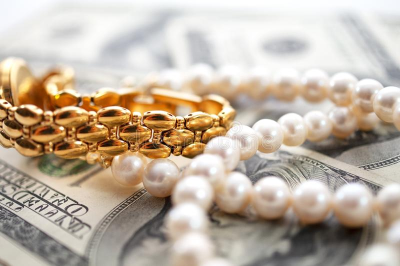Dollars background with gold watch and pearls conceptual image royalty free stock photography