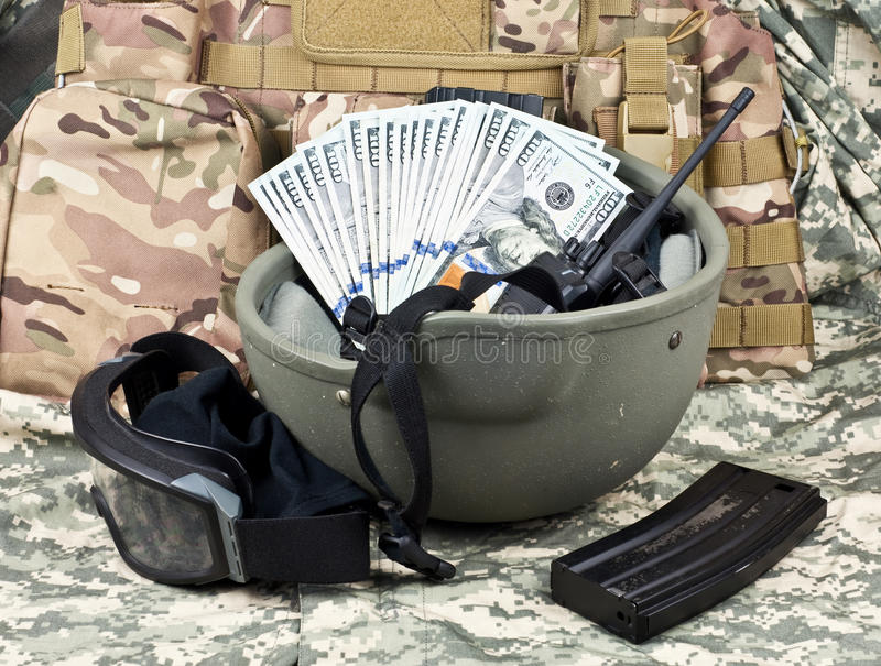 Dollars on a background of military equipment. Dollar bills against the background of military equipment stock photography