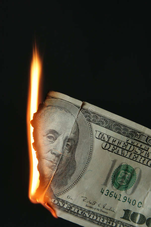 Dollars bill on fire. One hundred dollars bill on fire over black background royalty free stock image