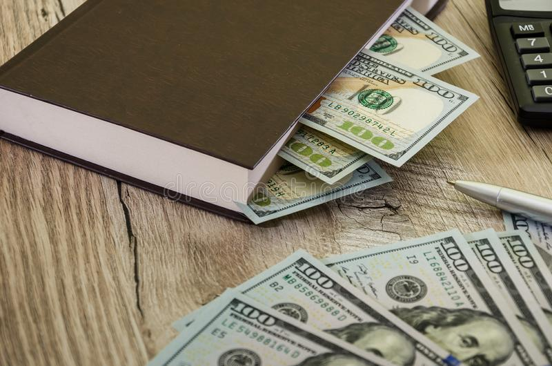 Dollars in a book, calculator and pen on a wooden background, close-up royalty free stock images