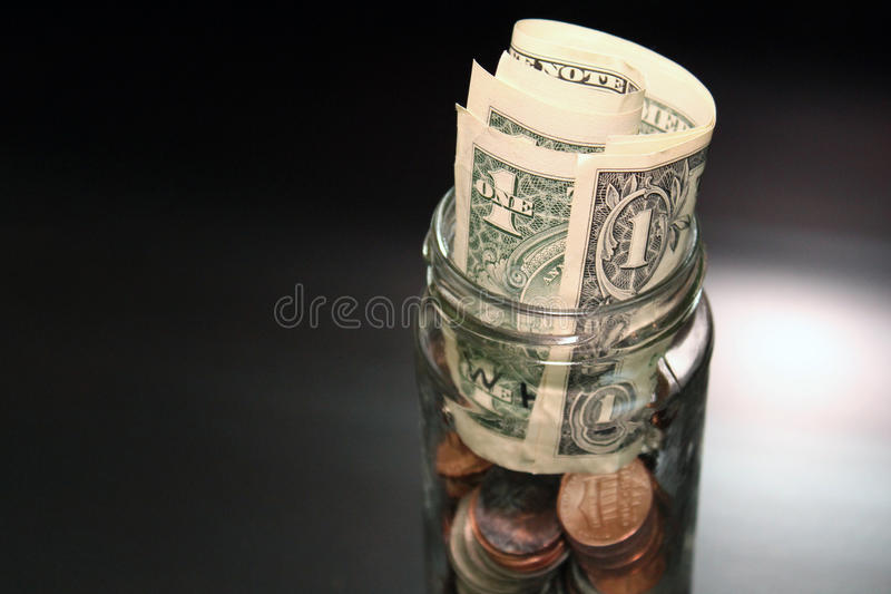 Dollars and cents. Pocket change dollars and cents in jar stock photos