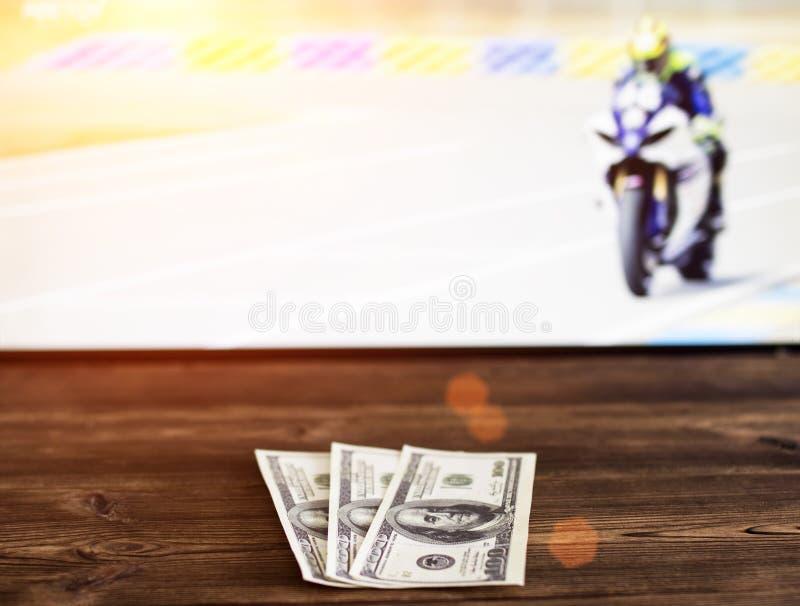 Dollars d'argent sur le fond de la TV sur laquelle moto d'exposition emballant, sports pariant, bookmaker image stock