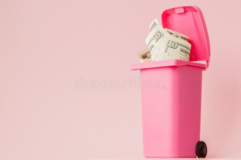 Dollars de billets de banque dans la poubelle rose de déchets sur le fond rose images stock