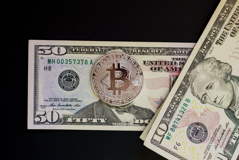 Dollars de billets de banque et pièce de monnaie argentée de bitcoin d'isolement sur le noir images libres de droits