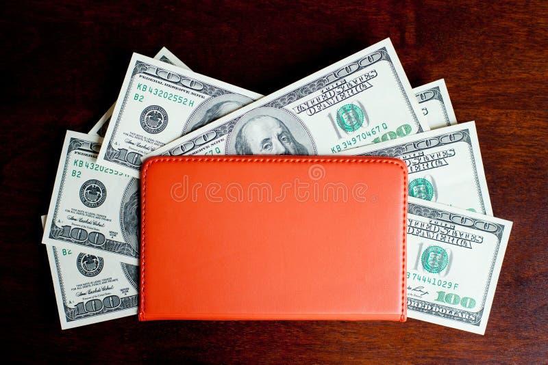 Dollars de billets de banque dans le carnet photos stock