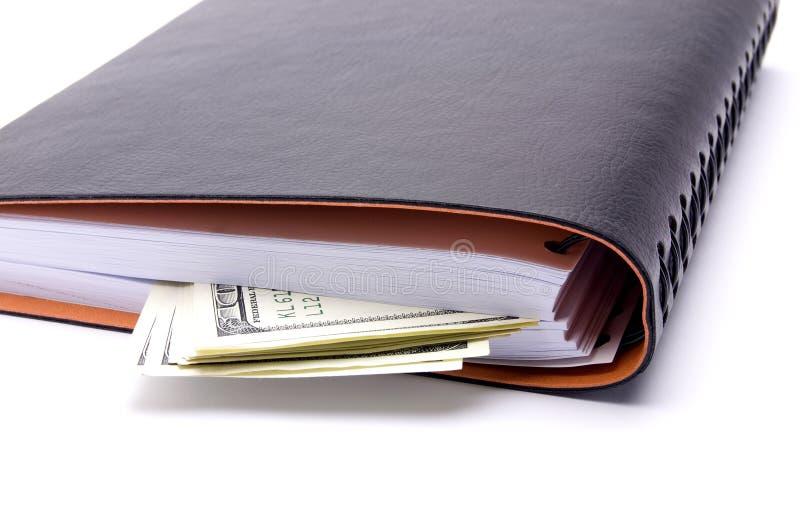 dollars en notitieboekje op een witte achtergrond stock foto