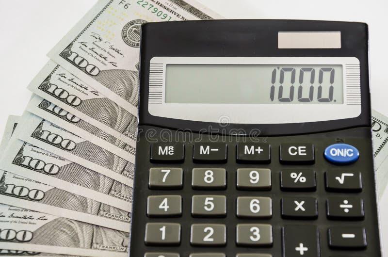 Dollars et calculatrice sur un fond blanc, en gros plan photo stock