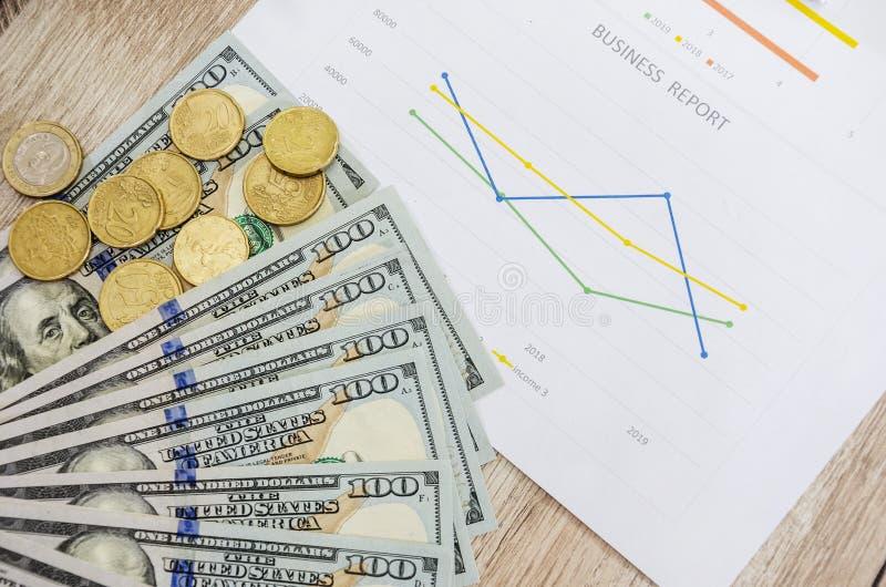 100 dollars et pièces de monnaie sur le graphique de gestion, plan rapproché photo libre de droits