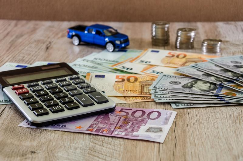 Dollars, euros, coins, a calculator and a toy blue car on a wooden background royalty free stock image