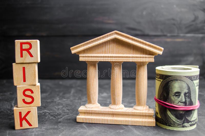 Dollars, government building and inscription `Risk` on wooden blocks.The risk of investing in a business project. Short-term inves. Tments. Withdrawal of capital stock photography